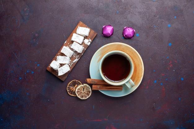 Vista superior de bombons de açúcar em pó delicioso torrão com chá na superfície escura