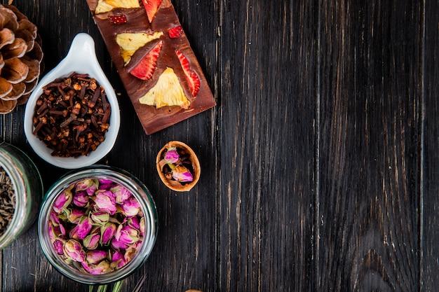 Vista superior de botões de rosa em uma jarra de vidro, especiarias cravo e barra de chocolate com frutas em madeira preta, com espaço de cópia