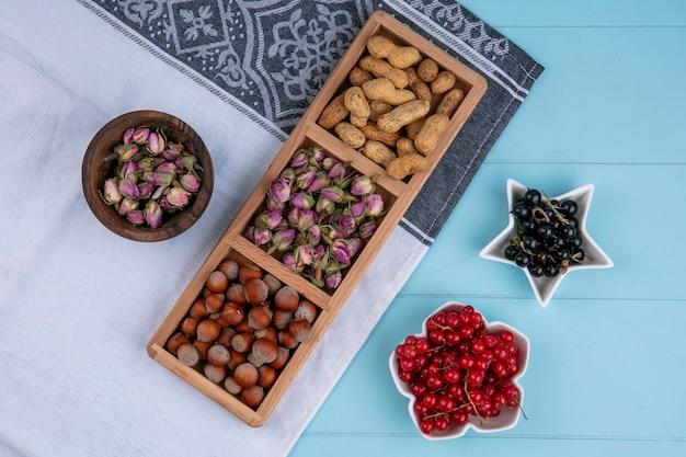 Vista superior de botões de rosa secos com avelãs e amendoim em uma toalha branca com groselhas vermelhas e pretas em uma superfície azul