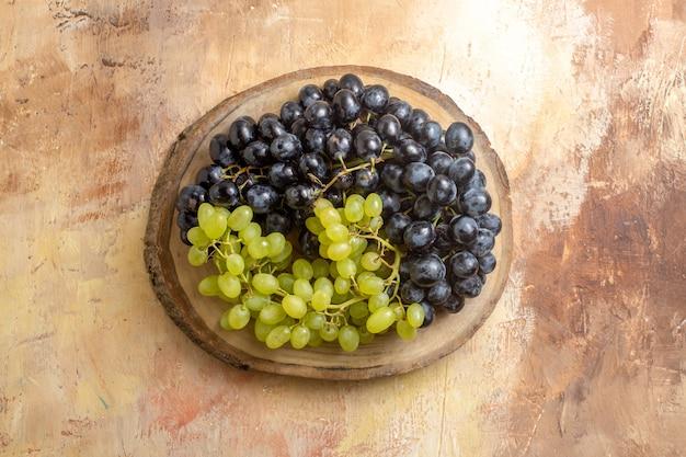 Vista superior de cachos de uvas verdes e pretas na mesa da cozinha