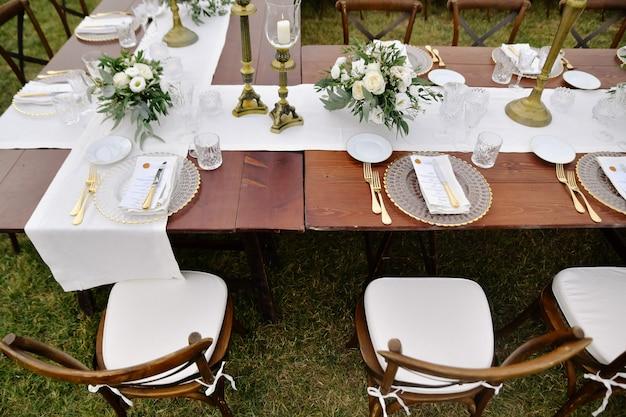 Vista superior de cadeiras marrons chiavari, copos e talheres na mesa de madeira ao ar livre, com buquês de branco eustomas
