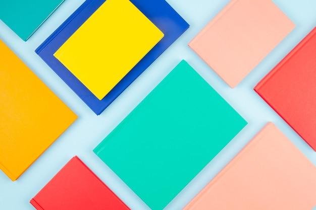 Vista superior de cadernos coloridos sobre a parede azul pastel. espaço de trabalho abstrato moderno, estudos, conceito de mesa de escritório