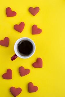 Vista superior de café preto e biscoitos em forma de coração vermelho na superfície amarela