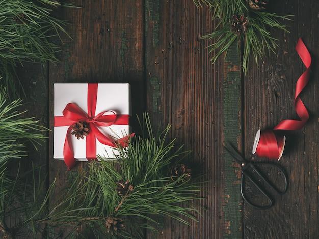 Vista superior, de, caixa branca, decorado, fita vermelha, com, abeto, e, pinho, cones, árvore
