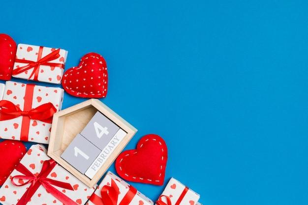 Vista superior de caixas de presente, calendário de madeira e corações vermelhos têxtil