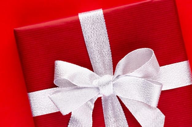 Vista superior de caixas de presente de natal embrulhadas e arrumadas com fitas na mesa vermelha
