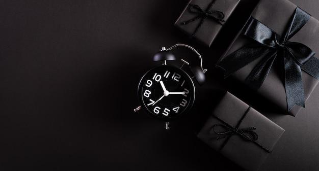 Vista superior de caixas de presente pretas com despertador