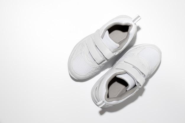 Vista superior de calçados esportivos infantis brancos com velcro e luz forte isolada no fundo branco