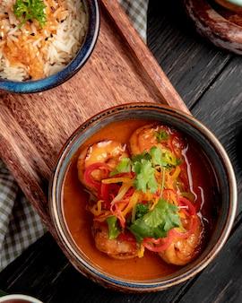 Vista superior de camarão frito com legumes e molho picante em uma tigela na placa de madeira em rústico