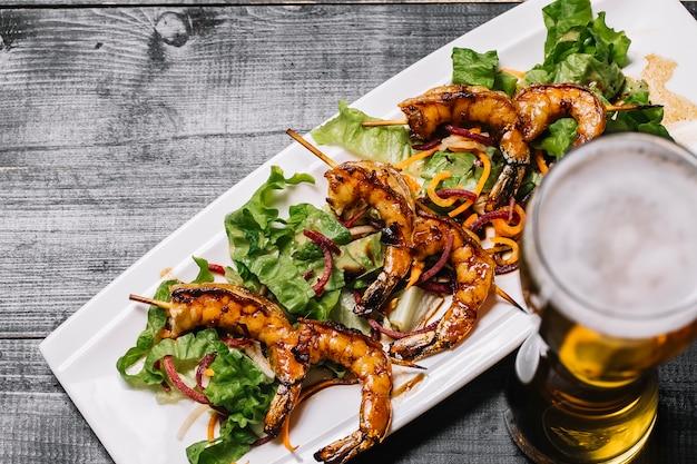 Vista superior de camarão grelhado no palito com folhas de salada e um copo de cerveja