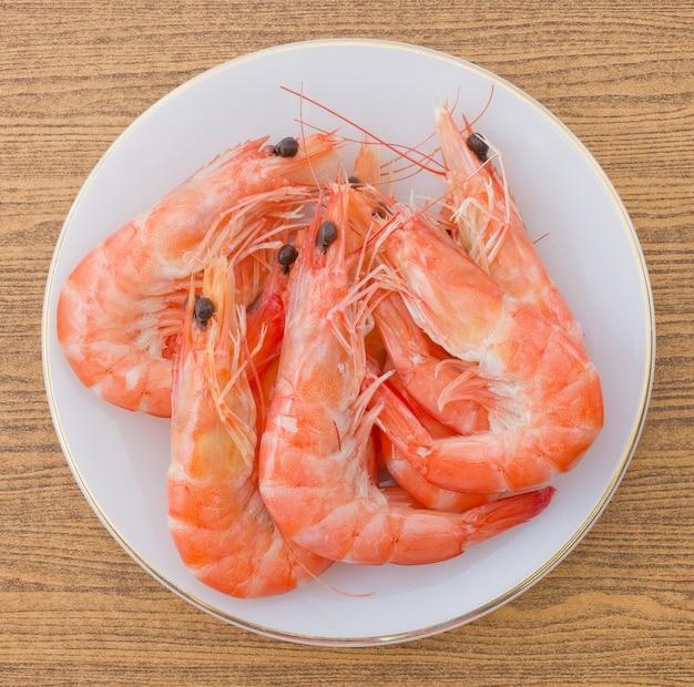 Vista superior de camarões cozinhados ou de camarões do tigre em uma placa branca.
