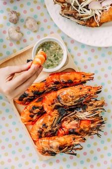 Vista superior de camarões grelhados tailandeses (camarões) no shell e mão mergulhando camarão em molho na bandeja de madeira, servido com molho picante de estilo tailandês.