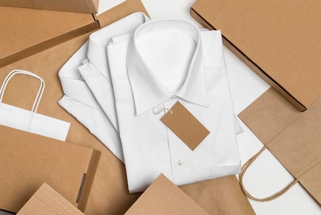 Vista superior de camisas dobradas com variedade de etiquetas de papelão em branco