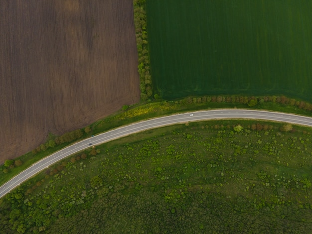Vista superior de campos verdes e estradas com carros se movendo ao longo da rodovia
