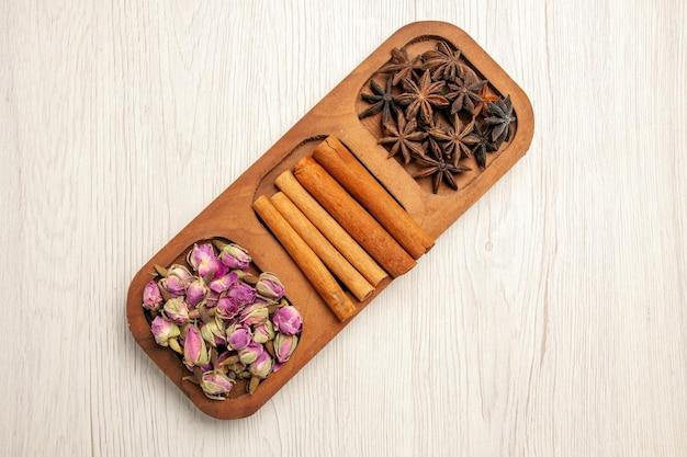 Vista superior de canela fresca com flores em cores de plantas de mesa brancas