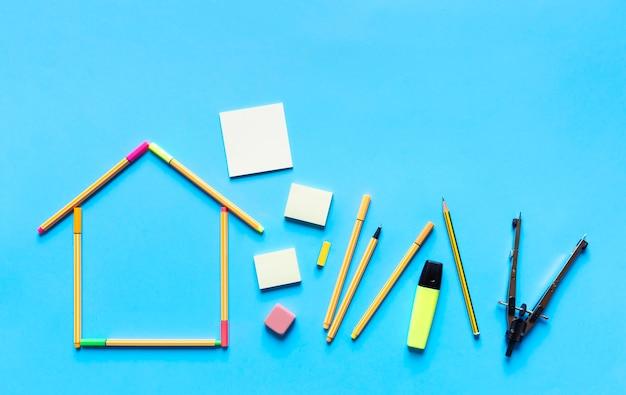 Vista superior de canetas fluorescentes formando o desenho de uma casa e outros materiais de papelaria em fundo azul pastel.
