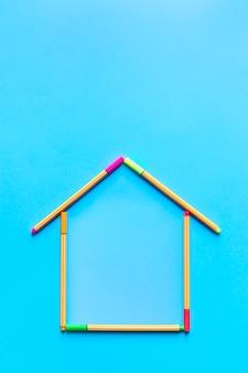 Vista superior de canetas fluorescentes formando o desenho de uma casa em fundo azul pastel.