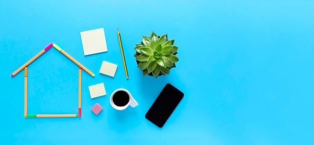 Vista superior de canetas fluorescentes formando o desenho de uma casa, uma xícara de café e smartphone em fundo azul pastel.