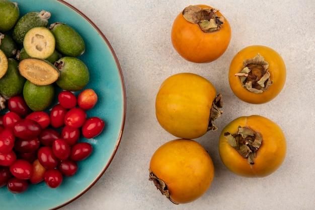 Vista superior de caquis alaranjados maduros com cerejas da cornalina e feijoas em um prato azul em uma parede cinza