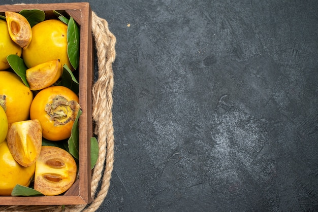 Vista superior de caquis doces frescos dentro de uma caixa na mesa escura, frutas maduras