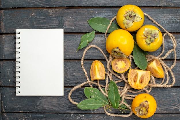 Vista superior de caquis doces frescos em uma mesa rústica de madeira, frutas maduras