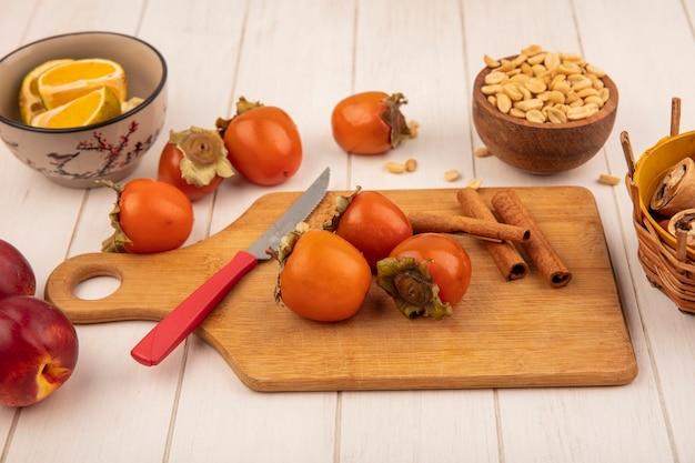 Vista superior de caquis em uma placa de cozinha de madeira com paus de canela com faca com amendoim em uma tigela de madeira com pêssegos isolados em um fundo branco de madeira