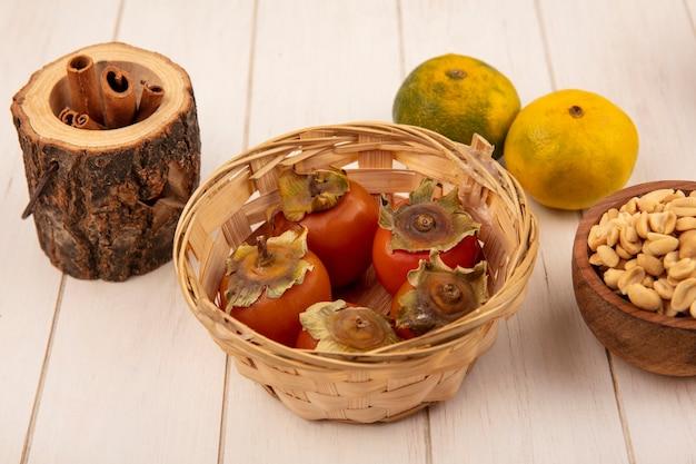Vista superior de caquis frescos em um balde com amendoim em uma tigela de madeira com tangerinas isoladas em uma parede de madeira branca