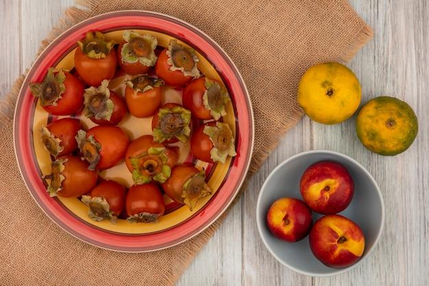 Vista superior de caquis frescos em um prato em um pano de saco com pêssegos em uma tigela com tangerinas isoladas em uma parede de madeira cinza