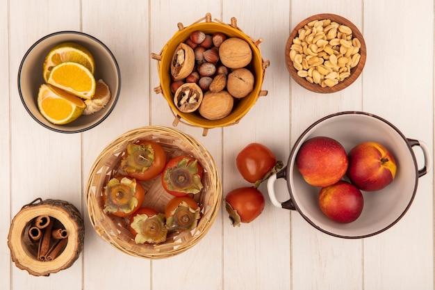 Vista superior de caquis macios e suculentos em um balde com pêssegos em uma tigela com nozes em um balde com paus de canela em uma parede de madeira branca