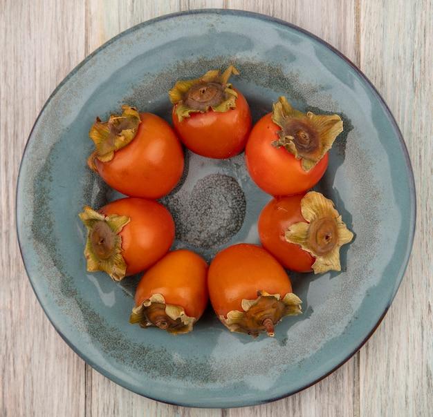 Vista superior de caquis macios e suculentos em um prato sobre uma superfície de madeira cinza