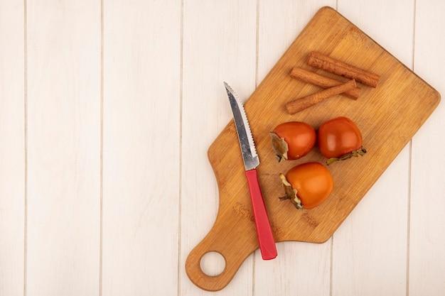 Vista superior de caquis macios em uma placa de cozinha de madeira com paus de canela e uma faca em uma superfície de madeira branca com espaço de cópia