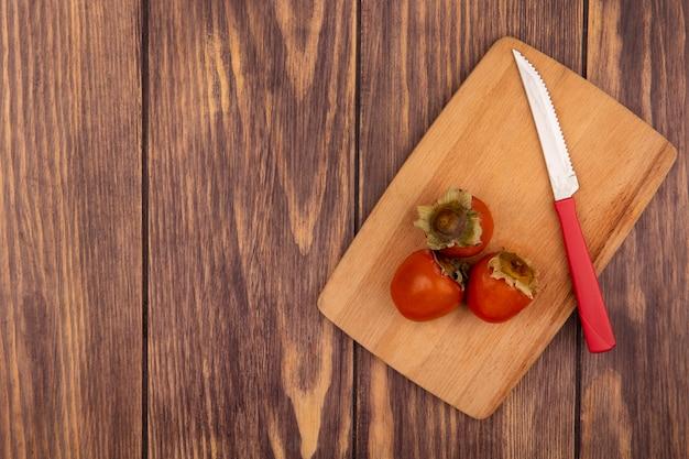 Vista superior de caquis macios em uma placa de cozinha de madeira com uma faca em um fundo de madeira com espaço de cópia