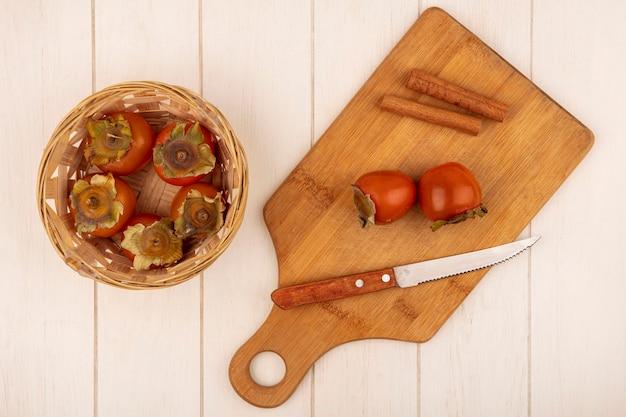 Vista superior de caquis suaves e suculentos em um balde com caquis em uma placa de cozinha de madeira com paus de canela em uma parede de madeira branca