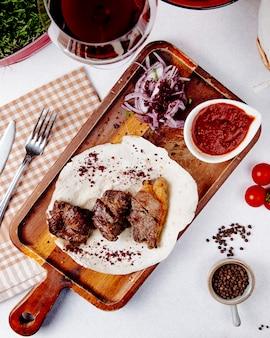Vista superior de carne assada com cebola roxa em uma placa de madeira