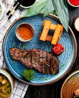 Vista superior de carne assada com molho picante e tomate grelhado com palitos de pão frito em um prato
