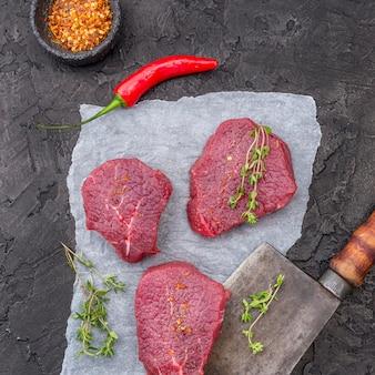 Vista superior de carne com ervas e cutelo