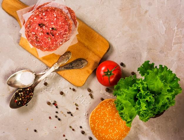 Vista superior de carne crua hambúrguer em uma mesa de madeira