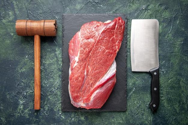 Vista superior de carne crua vermelha fresca em uma tábua de corte, martelo de madeira e machado em fundo de cor verde e preto