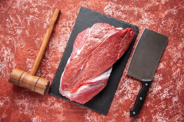 Vista superior de carne fresca crua vermelha em quadro preto, martelo de madeira marrom e machado em fundo vermelho pastel