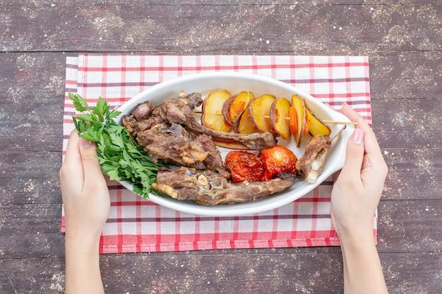 Vista superior de carne frita com verduras e ameixas assadas dentro do prato na mesa rústica marrom, comida refeição prato carne jantar vegetais