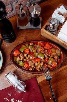 Vista superior de carne frita e legumes em uma mesa de madeira