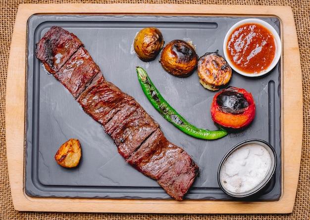 Vista superior de carne grelhada com batatas e legumes grelhados com ketchup e maionese