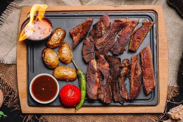Vista superior de carne grelhada com batatas e legumes grelhados com molhos