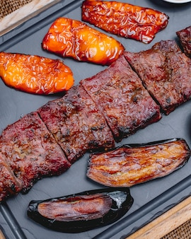 Vista superior de carne grelhada com pimentão e berinjela grelhada em uma bandeja