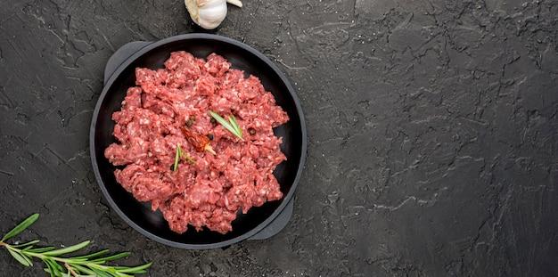 Vista superior de carne no prato com ervas e cópia espaço