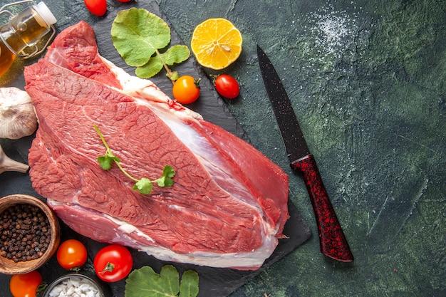 Vista superior de carne vermelha crua fresca em bandeja de pimenta preta de vegetais caídos faca de garrafa de óleo em fundo de cor escura