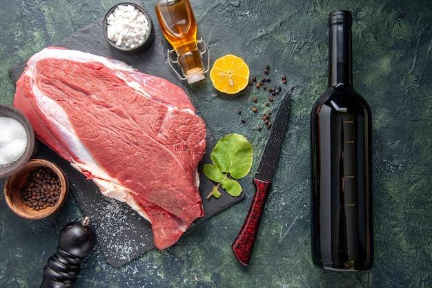 Vista superior de carne vermelha crua fresca na bandeja de pimenta preta, limão e óleo de martelo de madeira, garrafa de vinho com fundo de cor escura