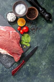 Vista superior de carne vermelha crua fresca na bandeja pimenta preta sal limão faca martelo de madeira em fundo de cor escura