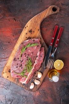 Vista superior de carne vermelha em uma tábua de corte de madeira e garfo e faca de garrafa de óleo de pimenta verde de alho em fundo escuro