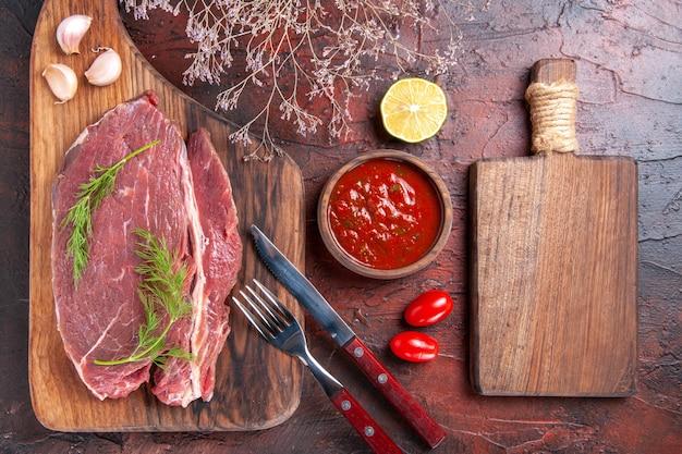 Vista superior de carne vermelha em uma tábua de corte de madeira e ketchup em uma tigela pequena, garfo e faca em fundo escuro.